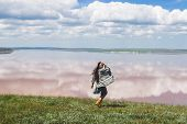 Happy Woman Running By The Lake Shore In Springtime. Grey Cardigan And Long Black Hair poster