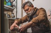 Selective Focus Of Senior Cobbler Fixing Sole To Shoe In Workshop poster