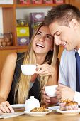 Happy woman sitting with man in caf�?�© drinking a cup of coffee