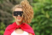 stock photo of teen pony tail  - smilling young woman with pony tail wearing a red super hero kit - JPG