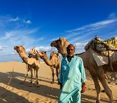 Rajasthan travel background - Indian man cameleer (camel driver) portrait with camels in dunes of Thar desert. Jaisalmer, Rajasthan, India