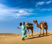 Rajasthan travel background - Indian cameleer (camel driver) with camels in dunes of Thar desert. Ja
