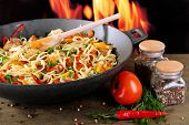 Noodles with vegetables on wok on fire background