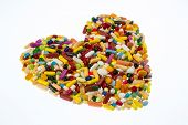 colorful tablets arranged in heart shape, symbol photo for heart disease, medication and pharmaceuti