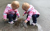 One year old twin girls playing with a puddle of water.