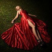 foto of superstars  - Beautiful Lady In Red Dress Lying On Green Grass - JPG