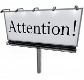 The word Attention on a big outdoor advertisement billboard to communicate a special announcement or