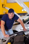 happy auto mechanic at work inside garage