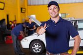 pic of auto garage  - happy male auto mechanic giving thumb up holding wrench - JPG
