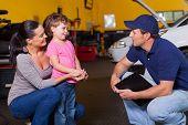 freundliche Auto-Techniker im Gespräch mit Kunden kleine Tochter in garage