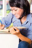 Schüler - junge Frau oder ein Mädchen sitzend mit Bücher in einer Bibliothek, lernen, sie macht Notizen