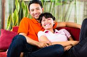 Indonesian couple sitting cozy at home on the sofa and relaxing