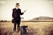 Handsome business man standing in a field with his suitcase and cell phone.