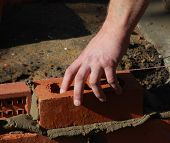 Close up of construction worker's hand pressing brick into place.