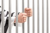 stock photo of prison uniform  - Male hands holding prison bars - JPG