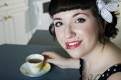 stock photo of rockabilly  - A rockabilly style girl enjoying her herbal tea - JPG