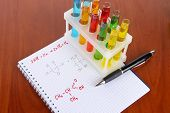 Test tubes with colorful liquids and formulas on table