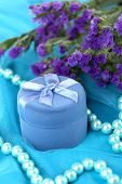 Bloemen en verlovingsring vak op blauw doek