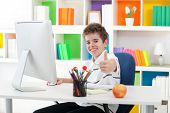 Boy sitting front of computer and showing thumb up