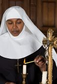 Mature nun lighting a candle on the altar of a medieval church