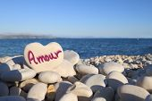 �?�¢??Amour�?�¢?�?� written on heart shaped stone on the beach