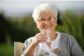stock photo of geriatric  - Senior woman with a glass of water - JPG