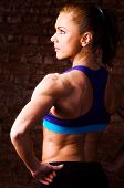 strong woman is posing against brick wall