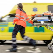 Running blurry paramedic woman rolling stretcher outside of ambulance car