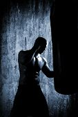 stock photo of heavy bag  - boxer man during boxing hiting heavy bag at training fitness gym - JPG