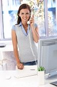 Female casual office worker talking on landline phone, smiling.