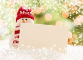 Cute Snowman with Scarf and Hat Next To Blank White Card Over Abstract Snow and Light Background