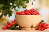 pic of barberry  - ripe barberries in wooden bowl with green leaves - JPG