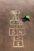 picture of hopscotch  - Hopscotch game drawn on the asphalt and kids rucksack laying nearby - JPG