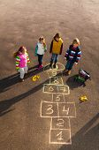 stock photo of hopscotch  - Group of kids jumping on the Hopscotch game drawn on the asphalt after school wearing autumn clothes after school - JPG