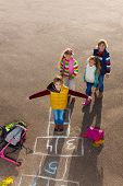 Boy With Friends Play Hopscotch
