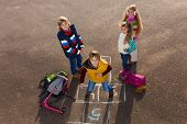 image of hopscotch  - Happy boy jumping on hopscotch game with friends boys an girls standing by with school bags laying near - JPG