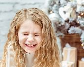 Adorable Blond Little Girl With Closed Eyes Sitting Under The Christmas Tree And Laughing