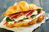pic of brie cheese  - Croissant with ham and brie cheese on white parchment - JPG