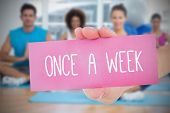 Woman holding pink card saying once a week against fitness class in gym