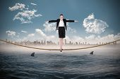 Businesswoman performing a balancing act against cityscape on horizon over shark infested sea