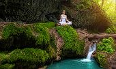 Woman practices yoga in nature the waterfall. sukhasana pose