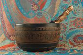 stock photo of tibetan  - metal Tibetan singing bowl against the backdrop of Indian fabrics - JPG