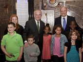 NEW YORK-APR 21, 2014: Police Commissioner William Bratton and children of honored NYPD officers at ceremony to light the Empire State Building in blue and purple in honor of Police Memorial Week.