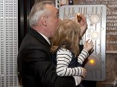 NEW YORK-APR 21, 2014: Police Commissioner William Bratton gets help from the daughter of an honored