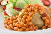 Detail of a jacket potato with baked beans and a out of focus salad.