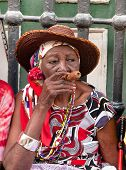 HAVANA - MAY 15: Old lady with a cigar dressed in typical cuban clothes on May 15, 2013. Iconic char