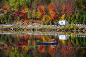 Camper driving though fall forest with colorful autumn leaves reflecting in lake. Highway 60 at Lake of Two Rivers, Algonquin Park, Ontario, Canada.
