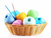 Colorful yarn for knitting in wicker basket and crochet hook, isolated on white