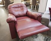 stock photo of recliner  - Red leather reclining armchair in furniture show room - JPG