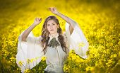 Young girl wearing elegant white blouse posing in canola field, outdoor shot. Beautiful girl